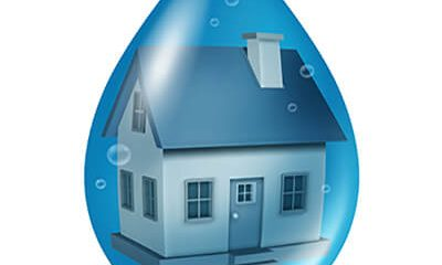 Flood insurance concept and water damage to a residential home with a house floating in a blue drop of liquid as a symbol of flooding problems isolated on a white background.